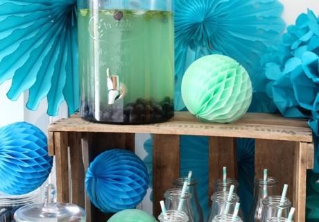Beim Sweet Table in Aqua-Tönen kommen Papierfächer, Wabenbälle und Pom Poms perfekt zum Einsatz.